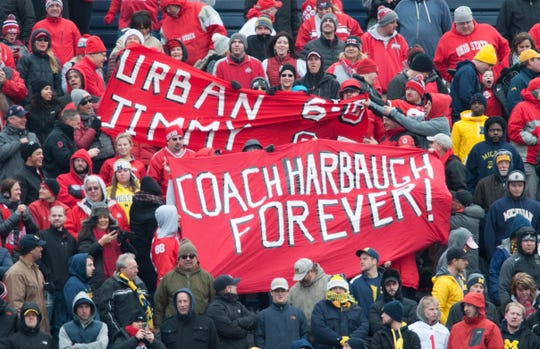 FILE -2017- These Ohio State fans in the upper reaches of the Big House love Michigan coach Jim Harbaugh. So far, Harbaugh is 0-3 coaching against the Buckeyes after a 31-20 loss in the 2017 game in Ann Arbor.