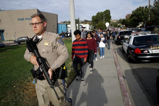 File-This Nov. 14, 2019, file photo shows students being escorted out of Saugus High School after reports of a shooting in Santa Clarita, Calif.