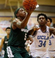 Michigan State guard Cassius Winston (5) heads for the basket ahead of  UCLA guard David Singleton (34) during the first half Wednesday in Lahaina, Hawaii.