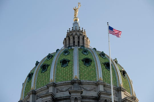 FILE- In this Jan. 15, 2019, file photo an America flag flies at the Pennsylvania Capitol building in Harrisburg, Pa.