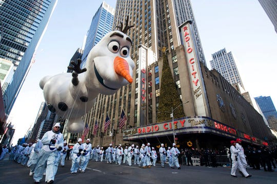 In this Nov. 22, 2018 file photo, the Olaf balloon floats past Radio City Music Hall during the 92nd annual Macy's Thanksgiving Day Parade in New York.  Macy's Thanksgiving Day Parade on Thursday, Nov. 28, 2019, will take place amid strong winds that could potentially ground the giant character balloons. The balloons have caused mishaps and injuries in the past when gusts blew them off course.
