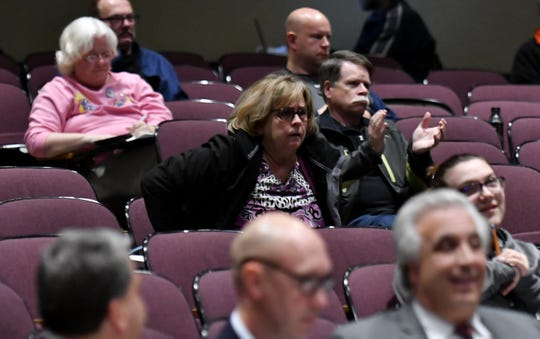 Doug DiCicco, 60, of Warren, at right, applauds with a few other residents after the vote to rescind a Council action taken on Sept. 10 regarding free lifetime health benefits to several outgoing council members at the Warren City Council meeting at the Warren Community Center in Warren on Nov. 26.