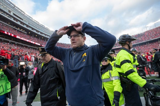 Michigan head coach Jim Harbaugh walks off the field after a lopsided 62-39 loss to Ohio State in Columbus last season.