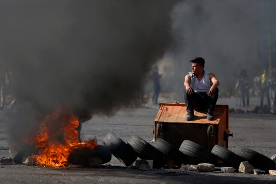 Palestinian demonstrators burn tires as they clash with Israeli troops during the protest against the U.S. announcement that it no longer believes Israeli settlements violate international law., at checkpoint Beit El near the West Bank city of Ramallah, Tuesday, Nov. 26, 2019.