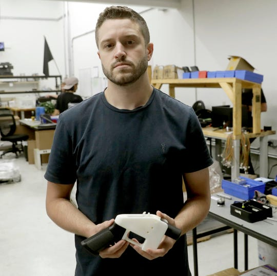 FILE - In this Aug. 1, 2018, file photo, Cody Wilson, with Defense Distributed, holds a 3D-printed gun called the Liberator at his shop, in Austin, Texas.