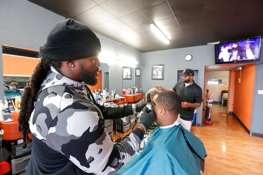 Darius Nunn talks about the impeachment hearings at his barber shop Friday, Nov. 22, 2019, in Racine, Wis.