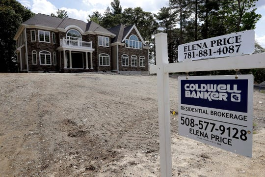 FILE - In this Sept. 3, 2019 file photo a sign rests in front of a newly constructed home, in Westwood, Mass. On Tuesday, Nov. 26, the Commerce Department reports on sales of new homes in October.