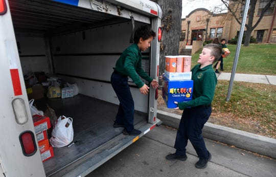 Jaden Schaffer carries boxes as he and his fellow students load a trailer full of food and various items from their Silent Heroes campaign at St. Joseph's Catholic School in Fort Collins, Colo. on Monday, Nov. 25, 2019. Inspired by his aunt in the National Guard, Schaffer started the campaign to send care packages to local men and women serving in the Middle East.