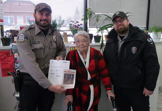 Florence Teeters, 104, poses with DNR wardens Joe Paul, left, and Nick Hefter after getting her deer hunting license.