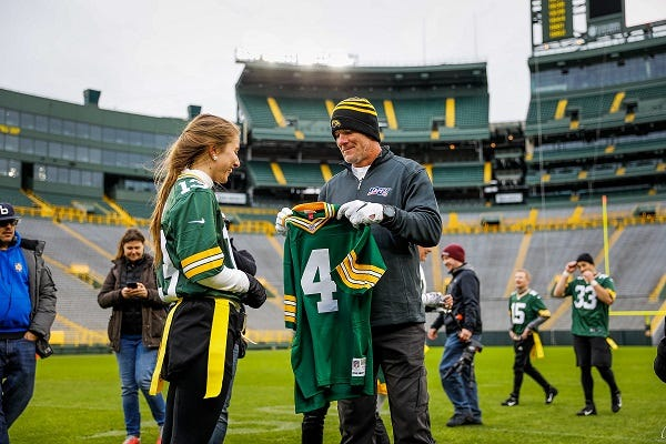 Former Packers quarterback Brett Favre gives an autographed jersey to Makenna Leyden. The Leyden family won a contest to have their annual backyard Turkey Bowl held at Lambeau Field this year. They played on Tuesday, Nov. 27, 2019.