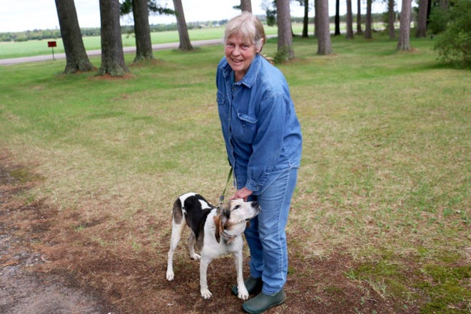 Laurie Groskopf is seen with her dog outside her home near Tomahawk, Wis., on May 28, 2019. Groskopf has lost two hunting dogs to attacks by gray wolves, which the federal government lists as an endangered species in the western Great Lakes region. She said $5,000 in payments from a Wisconsin Department of Natural Resources wolf damage compensation fund could not make up for the loss of animals she treated as family.