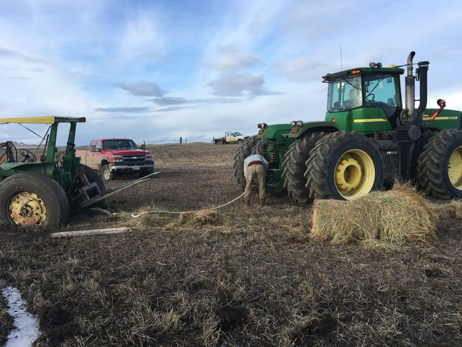 Zane Drishinski called in reinforcements to get Lisa Schmidt's tractor out of the mud. Colby Johns saved a lot of shovel work when he brought his tractor to help.