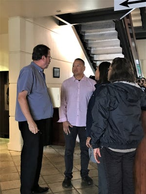 Attorney F. Randall Cunliffe, left, speaks to his client, Jason Oscar Susuico, second from left,  after his arraignment on Wednesday, Nov. 27, 2019, in the Guam Judicial Center.