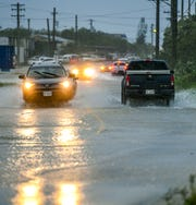 Motorists navigate through the flooded roadway of Adrian Sanchez Street, also known as Hamburger Road, after the passage of Tropical Storm Kammuri on Wednesday, Nov. 27, 2019.