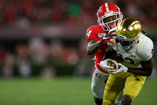 Notre Dame Fighting Irish wide receiver Lawrence Keys III (13) catches a pass against Georgia Bulldogs defensive back DJ Daniel (14) in the second quarter at Sanford Stadium on Sept. 21, 2019.