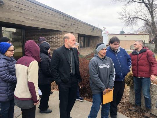Bishop Thomas Zinkula and Father Guillermo Treviño accompany Alejandro Guzman after his ICE check-in in Cedar Rapids Nov. 27, 2019.