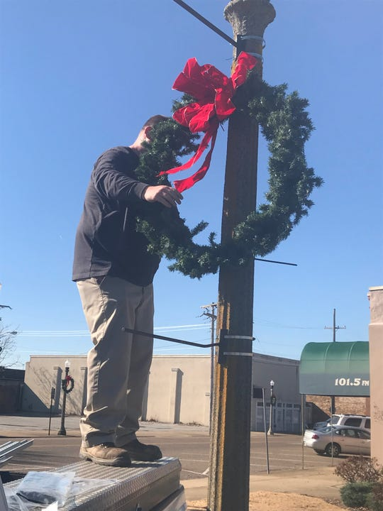 An employee of the City of Jackson hangs a Christmas wreath on a light post at the corner of Shannon and Lafayette in Downtown Jackson on Nov. 19.