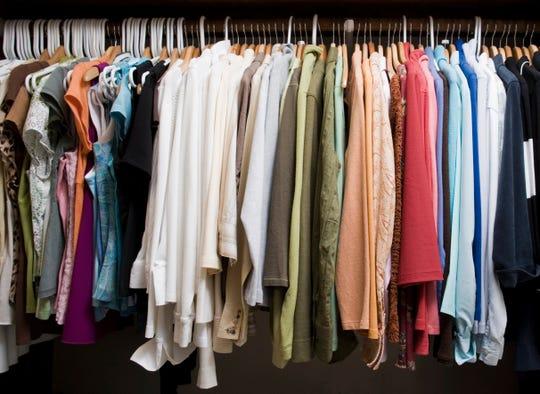 A closet filled with women's vest and coats hanging on hardwood oak coat hangers.