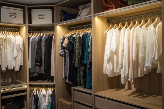 Luxury walk in closet / dressing room with lighting and jewel display. Dresses, handbags, blouses and sweaters on hangers in the wardrobes.