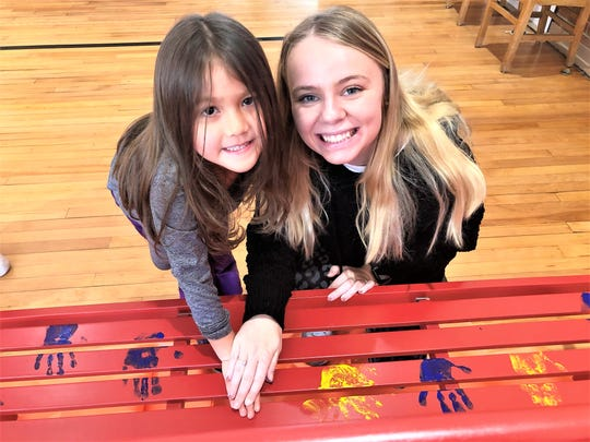 Kindergartner Lorraine Land helps decorate the new buddy bench at South Knoxville Elementary with the help of UT student Hailee Brown on Nov. 25.