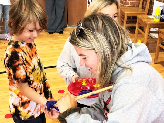 UT student Kellie Costello paints South Knoxville Elementary student Finn Delaney's palm before he decorates the new buddy bench on Nov. 25.