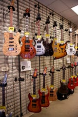 Electric guitars hang on a wall inside Klaverenga Guitar and Piano Studio, 521 Main St., Wednesday, Nov. 27, 2019 in Lafayette. The shop first opened in 1985, but moved to their current location in 1992.