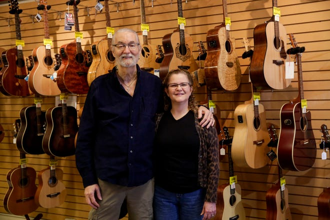 Owners Jim and Julia Klaverenga pose for a portrait with a row of guitars hanging behind them inside their Main Street business, Klaverenga Guitar and Piano Studio, Wednesday, Nov. 27, 2019 in Lafayette. Klaverenga Guitar shop first opened in 1985, but moved to their current location in 1992.