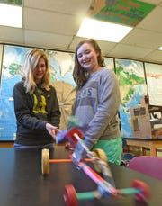 Kyleigh Weiser and Piper McManes made a car propelled by rubber bands for teacher Anne Petrie's lesson on Newton's three laws of motion.