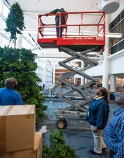 Montgomery Regional Airport employee Shirley Rogers looks on as the airport Christmas tree is put up at the airport in Montgomery, Ala., on Wednesday, November 27, 2019.