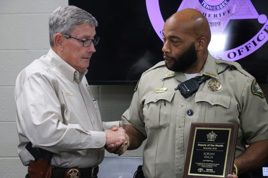 Adrian Finch shakes hands with WCSO Sheriff Dusty Rhodes after receiving his award on Nov. 26, 2019.
