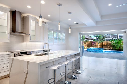 The gourmet kitchen is highlighted by stainless steel appliances, white cabinetry and a large center island with with a quartz countertop and casual seating.