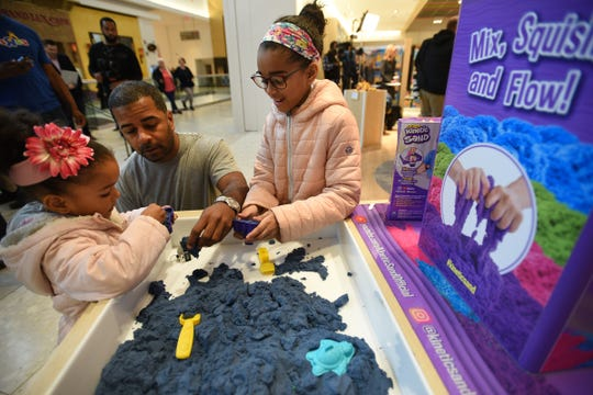 Johnny Rodriguez of Paterson plays with his two daughters Valentina (3, L) and Averly (9, R) during the grand opening at Garden State Plaza Mall in Paramus on 11/27/19.