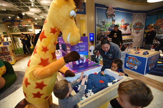 Geoffrey, the brand's giraffe mascot, plays with children during the grand opening at Garden State Plaza Mall in Paramus on 11/27/19.