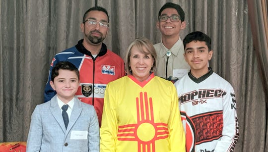 Pictured with Governor Michelle Lujan Grisham are, clockwise from bottom, Uriah Nordorf, James Baca, Mykal Carlos and Xavier Baca.