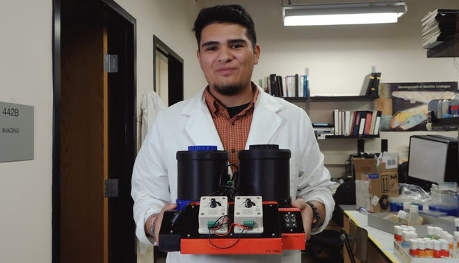 Luke Sanchez, a biology major and student regent at New Mexico State University, is using flies to study degeneration in eyes with the help of student engineers from the Aggie Innovation Space. Sanchez holds the machine developed by AIS Innovators.