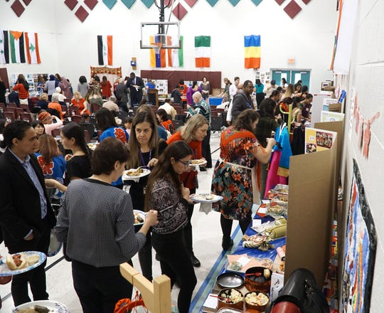 ESL students and guests check out information from their fellow students' countries and some of their fare they've cooked up on Nov. 27.