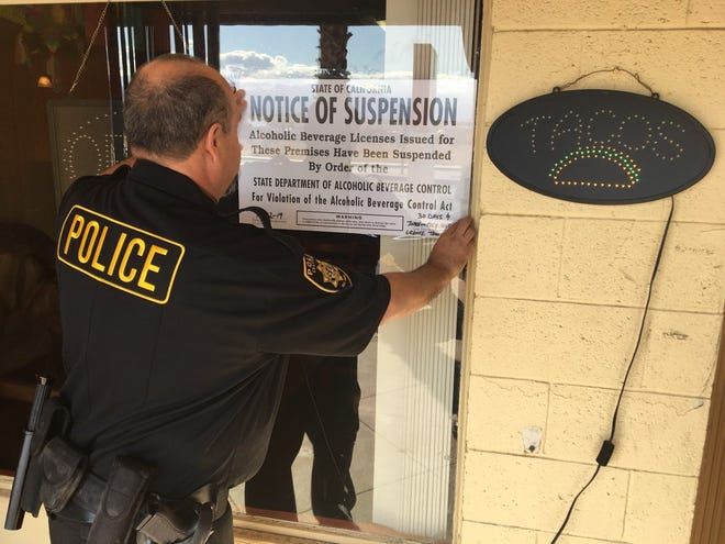An agent with the state Department of Alcohol Beverage Control posts a notice of suspension on the window of Mundo's Mexican Grill, at 72-390 Ramon Road, Thousand Palms.