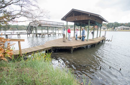 From left, Council of Neighborhood Association Presidents of Pensacola President Rand Hicks, Cordova Park on the Bayou Neighborhood Association Treasurer Doug Douglass and CPBNA President Kate Buffington and her husband, David Mitchell, chat on a dock on Bayou Texar in Pensacola on Wednesday.