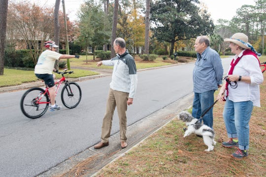 Council of Neighborhood Association Presidents of Pensacola President Rand Hicks, center, greets a passing bicyclist at Baars Park in Pensacola on Wednesday.