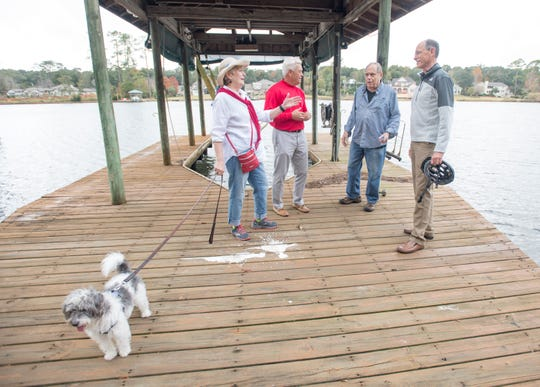 From left, Cordova Park on the Bayou Neighborhood Association President Kate Buffington, Council of Neighborhood Association Presidents of Pensacola Treasurer Doug Douglass, Buffington's husband, David Mitchell, and CNAPP President Rand Hicks chat on a dock on Bayou Texar in Pensacola on Wednesday.