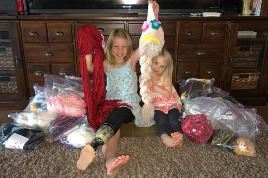 Abri Bentley and her sister Ariya with yarn wigs for children with cancer donated by Halo Keepers.