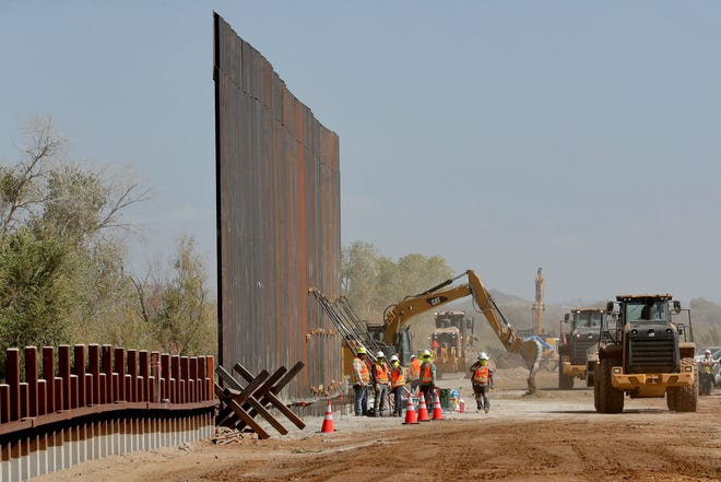 Government contractors erect a section of Pentagon-funded border wall along the Colorado River in Yuma, Ariz., in September 2019.