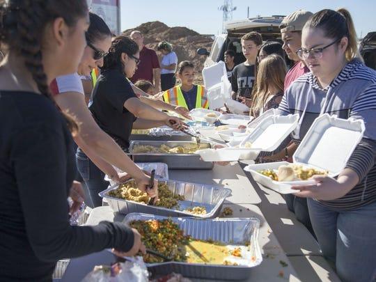 Los voluntarios preparan comida para las personas sin hogar en el Campus de Servicios Humanos en el Día de Acción de Gracias 2017 en Phoenix. Un lote vacío en el Campus de Servicios Humanos se convirtió en un centro de donaciones improvisado.