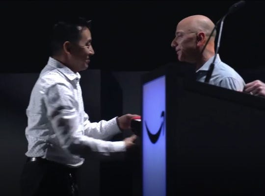 Former Nevada boxer Lawrence Tam receives an award from Jeff Bezos.