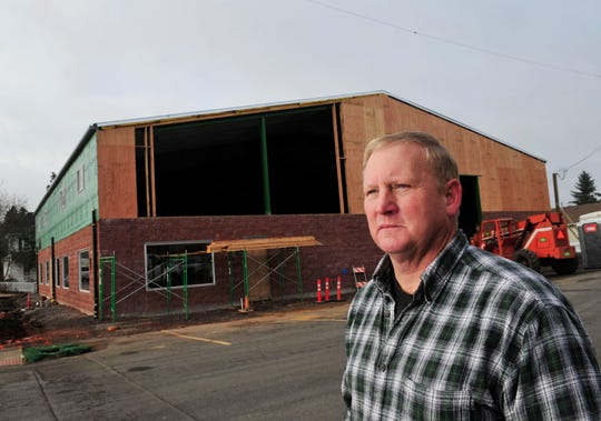 Doug Nichol, owner of T G Nichol Plumbing, stands next to his business as it's being rebuilt in Aumsville Wednesday, Dec. 7, 2011, nearly a year after a tornado ripped through town, tearing the roof off his building.