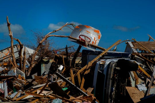 In this Sept. 27, 2019 file photo a basketball board is seen next to a car among the debris left by Hurricane Dorian, in a neighborhood destroyed by the storm in Abaco, Bahamas. Any concern about whether it was appropriate to be playing sports in the Bahamas while parts of the multi-island nation continue to recover from the effects of the storm was quickly dispelled by officials. Officials are hoping tourism and upcoming sporting events aid recovery efforts by boosting the economy to pay for reconstruction and raising awareness for people to donate or volunteer for ongoing work. Participants in those events _ including the eight-team Atlantis tournament opening Wednesday, Nov. 27, 2019 are also helping in the recovery. (