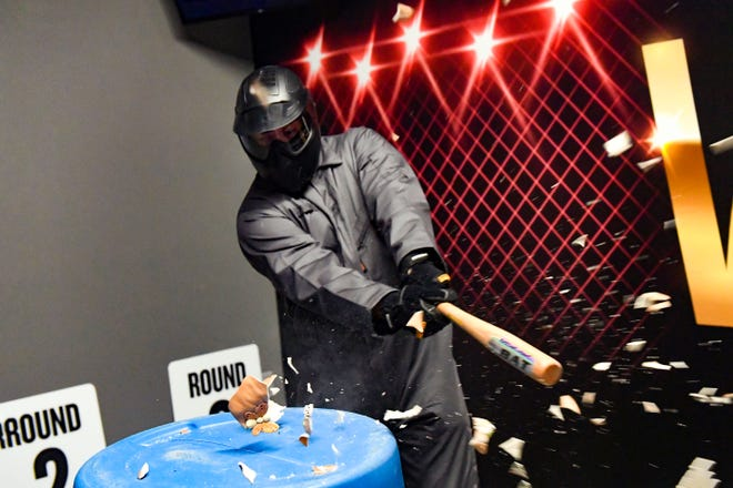 Doug Black, co-owner of Escapades Escape Rooms, smashes a small clay pot in the business' new rage room on Wednesday, Nov. 27, in Sioux Falls.