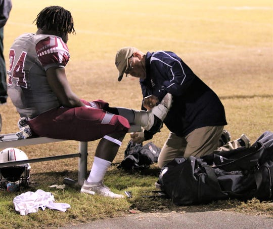 Tallahassee Orthopedic Clinic certified athletic trainer Jim Watson tapes up Madison County junior running back Robert Hiers, who suffered a high-ankle sprain several weeks before.