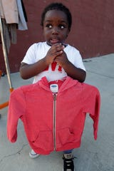 Bentley Lewis, 4, holds up his new red coat he picked up at a coat drive hosted by Destiny Church on Wednesday, Nov. 27, 2019.