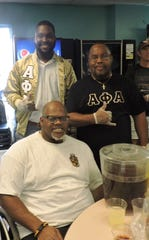 Alpha Phi Alpha Fraternity volunteers Kenzy Pierre-Louis, left, and Gerald Wilcox with Jimmy Washington, seated, at the Community Thanksgiving Dinner on Nov. 21, 2019, at the Gertrude Walden Child Care Center in East Stuart.